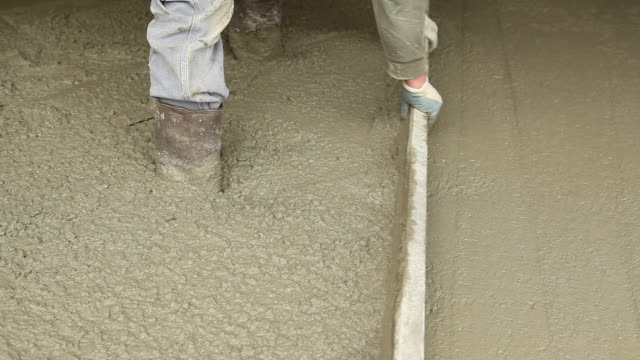Worker Using Hand Screed and Trowel to Smooth Concrete