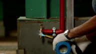 Worker using welding torch on tap