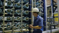 TS MS worker walking along rows of filters and tubing in water treatment plant, making notes on handheld electronic device, RED R3D 4K