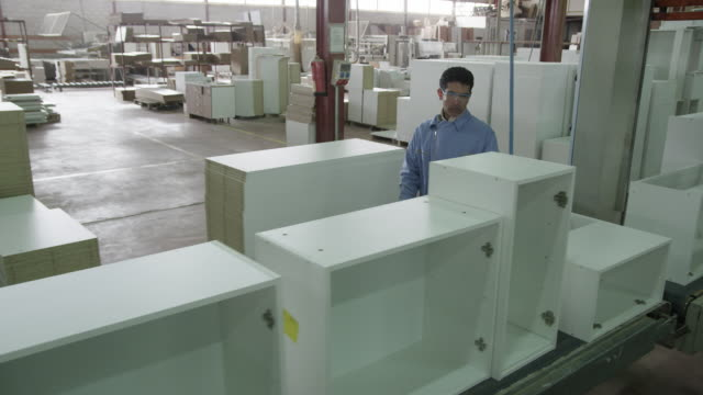 TS HA worker walking along semi-finished pieces of furniture on assembly line in furniture factory