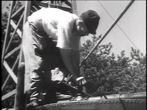 worker walking atop oil tanks / worker turning valve / oil refinery from above