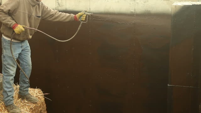 Worker Waterproofing a new House Foundation