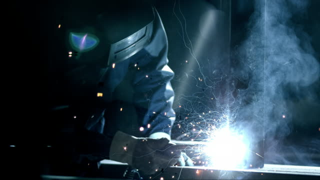 SLO MO Worker welding a metal frame