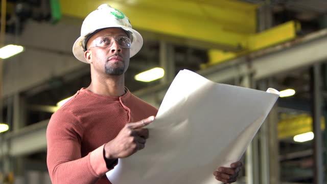 Arbeiter mit Bauarbeiterhelm Pläne betrachten