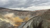 Workers and machines move through the Yanacocha gold mine located in northern Peru on October 26th 2015 Shots Wide shot of a controlled explosion in...