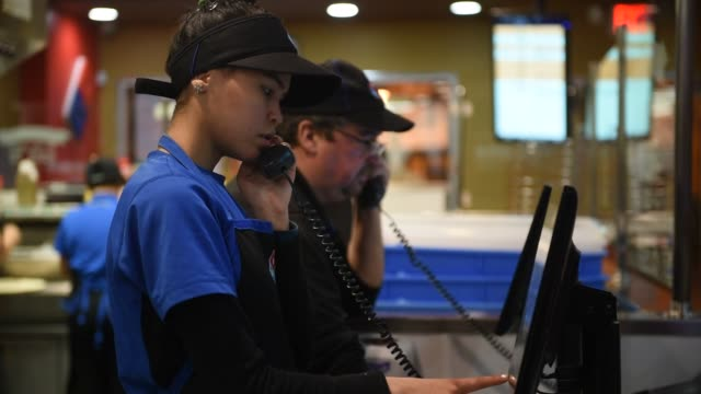 Workers answer phones at Domino's Pizza Theatre on 1st Street in Jersey City New Jersey US on February 20 Wide shots and close ups of a Hispanic...