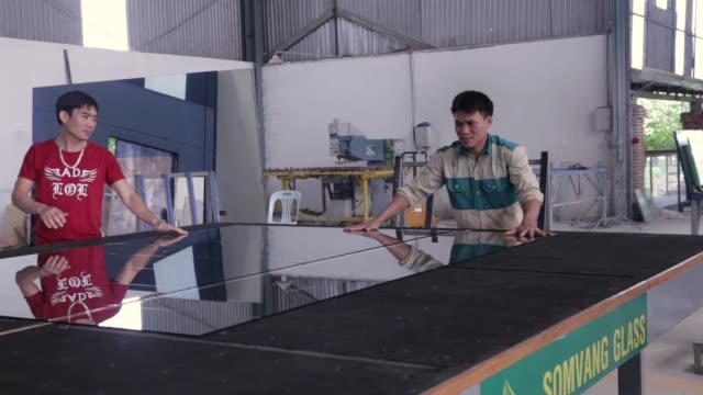 Workers arrange a sheets of glass on a cutting machine at the Somvang Glass Factory on the outskirts of Vientiane Laos on Wednesday Nov 1 Workers...