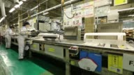 Workers assemble an indoor unit of a Daikin Industries Ltd split type air conditioner on the production line of the company's Shiga plant in Kusatsu...
