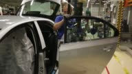 Workers attach doors to VW Tiguan automobiles on the production line at the Volkswagen Group Rus OOO plant in Kaluga Russia on Tuesday Sept 19 Newly...