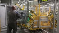 Workers carry the side panel of a VW Tiguan automobile onto the production line at the Volkswagen Group Rus OOO plant in Kaluga Russia on Tuesday...