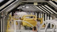 Workers check the bodywork of automobiles after passing through the paint shop at the Volkswagen Group Rus OOO plant in Kaluga Russia on Tuesday Sept...