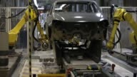 Workers check the bodywork of Skoda Auto AS Rapid automobiles after passing through the paint shop at the Volkswagen Group Rus OOO plant in Kaluga...