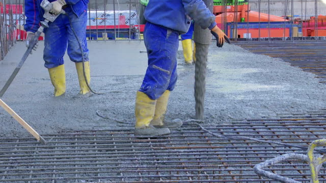Workers Directing Concrete Onto The Construction Site TL