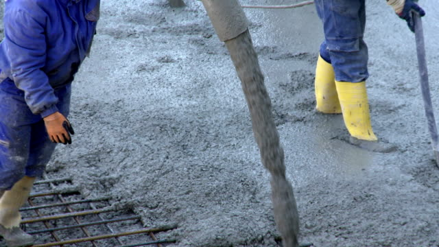 Workers Directing Concrete Onto The Construction Site