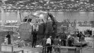 Workers examine a partially assembled front end of a Pan Am Boeing 707 being lifted and moved in a factory.