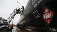 Workers fill oil tankers in Bakken North Dakota US on February 13 Wide shot and close ups of workers climbing to the top of oil tankers Wide shots...