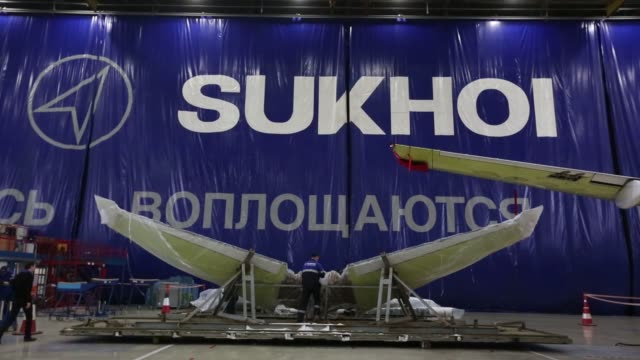 Workers fit front undercarriage systems to a Sukhoi Superjet 100 aircraft during construction at the Sukhoi Civil Aircraft Co final assembly plant in...