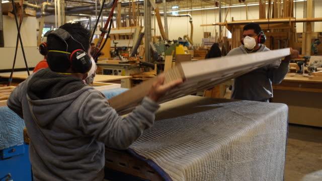 Workers flip custom wood door and begin sanding in woodworking shop