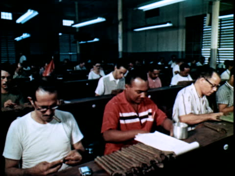 Workers in a Cuban cigar factory making cigars while listening to news of the day