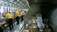 LD-Arbeiter im Lager unter Pakete abseits des Förderbandes