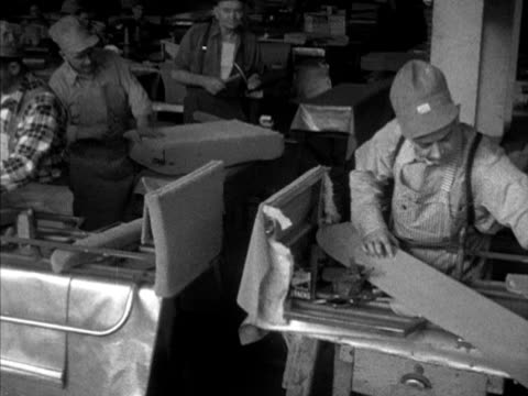 Workers in Union Pacific Upholstery Shop working on repairing reupholstering various passenger train car seats cushions Factory
