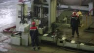 Workers inspect a cooling zinc ingot in the rotary foundry room at the Chelyabinsk Zinc Plant operated by Ural Mining and Metallurgical Co in...