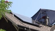 Workers installing solar panels on the roof of a suburban home various panning shots of solar panels Solar Panel Installation on September 10 2013 in...