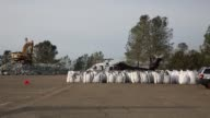 Workers load bags with rocks in preparation for emergency measures taken at the Oroville Dam after authorities warned that a spillway damage in North...