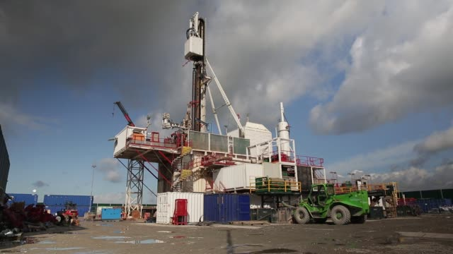 Workers look on from the control room as colleagues connect sections of pipe together on the drilling platform at the Preston New Road pilot gas well...