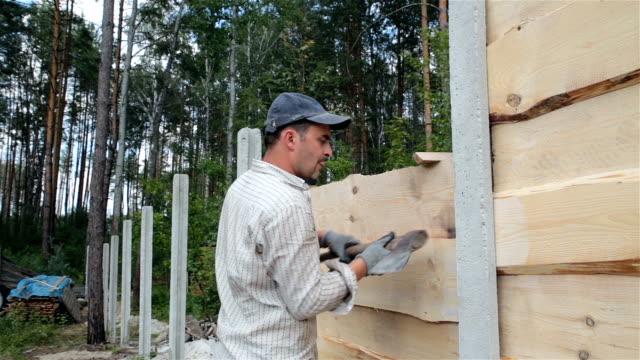 Werknemers maken een houten hek.