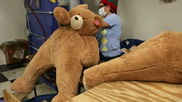 Workers make teddy bears at the Vermont Teddy Bear factory in Shelburne Vermont November 13 2015 Shots An employee wearing a face mask uses a hose to...