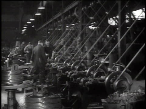 1938 WS workers managing machines that are spinning steel wire / Oakland, California, United States
