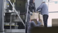 Workers packaging beer bottles into boxes