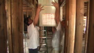 Workers passing a heating unit through a ceiling opening in a partially constructed home / New Orleans Louisiana United States