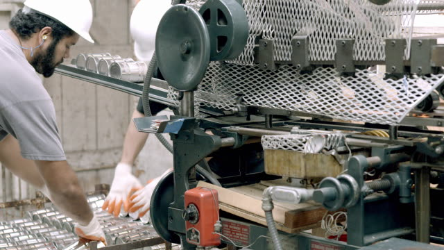 workers pick up freshly sealed cans of olives and place them on intake tray of vintage labeling machine at olive processing plant / Ontario, California, USA