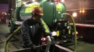 Workers pouring used cooking oil into a collection bin Workers with the San Francisco Water Power and Sewer's SFGreasecycle program dump bottles of...