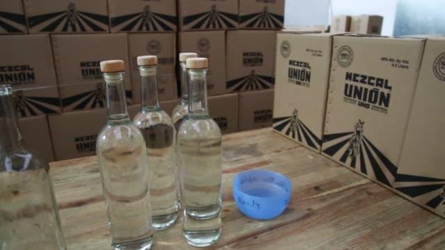 Workers prepare bottles of mezcal tequila inside the Mezcal Union distillery in Matatlan Oaxaca Mexico on August 19th Photographer Susana...