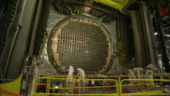 Workers refurbish tube channels on a nuclear reactor panel.