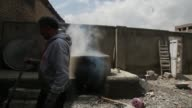 Workers separate skeins of wool used to weave carpets after they are dyed in a cauldron at a facility in Kabul Afghanistan Workers stir skeins of...