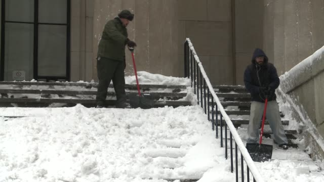 Workers shovels the sidewalks and steps of the Federal Hall National Memorial Building on Wall St / Tired man uses shovel to clear the heavy snow...