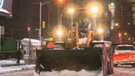 Workers take a breather from battling snow storm with snow plow / Man drags space heater across sidewalk