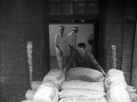 Workers unload sacks of flour and place them in a small lift at a biscuit factory