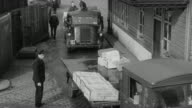 MONTAGE Workers unloading cargo from trucks and into freight cars for transporting / United Kingdom