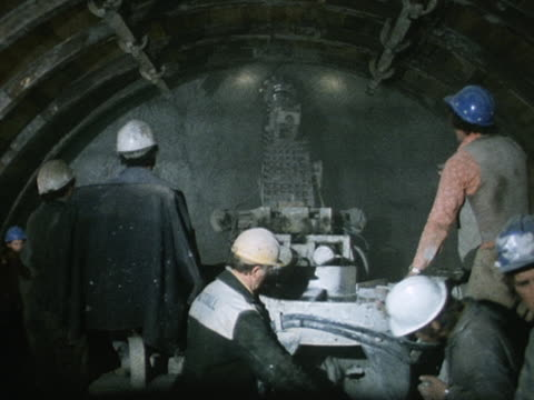 Workers use a boring machine to remove rocks in the preparatory tunnel at the Channel Tunnel project