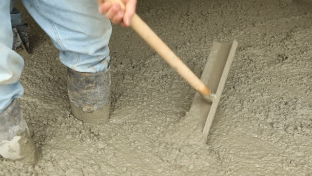 Workers Using Spreader Tools to Distribute Concrete