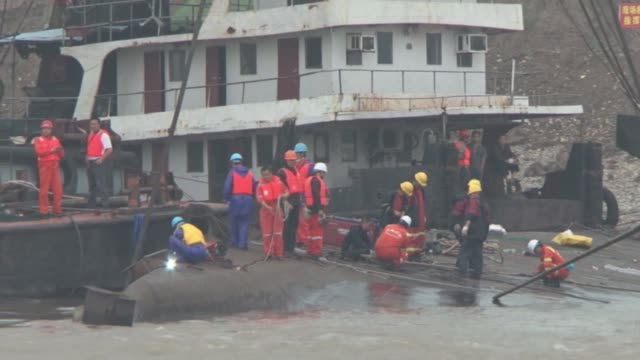 Workers weld the hull of the capsized cruise ship in China before it is lifted a risky operation that could destabilise the wreck and send it further...