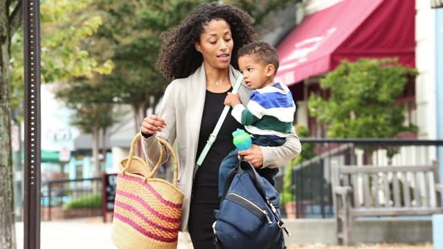 Working mother carrying son walking on urban sidewalk