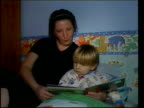 Working Mothers Effect on Children's Future ITN LIB Woman sitting on floor of lounge with her children CMS Young boy colouring in picture Woman...