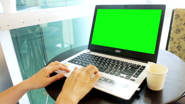 Working On Notebook Computer With Green Screen At Cafe