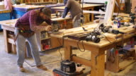 Workman operates hand-help power sander in woodworking shop